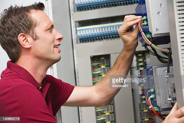Germany, Munich, Technician fixing cable wires of circuit board