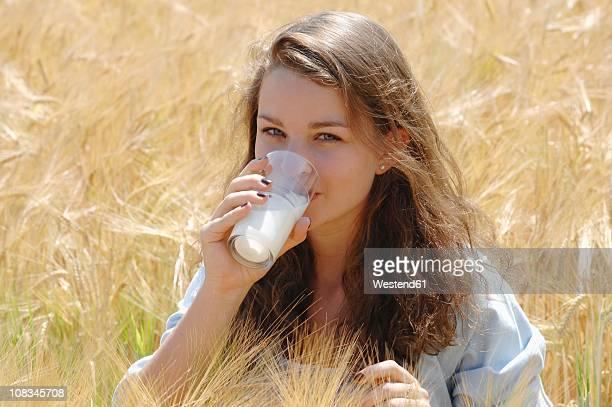Germany, Munich, Teenage girl drinking milk in cornfield