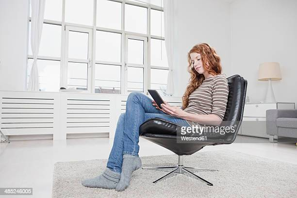 Germany, Munich, Woman at home, sitting in chair, reading e-book