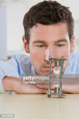 Germany, Munich, Businessman looking at hour glass on office desk, portrait
