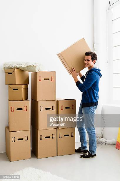 Germany, Munich, Young man holding cardboard box, smiling