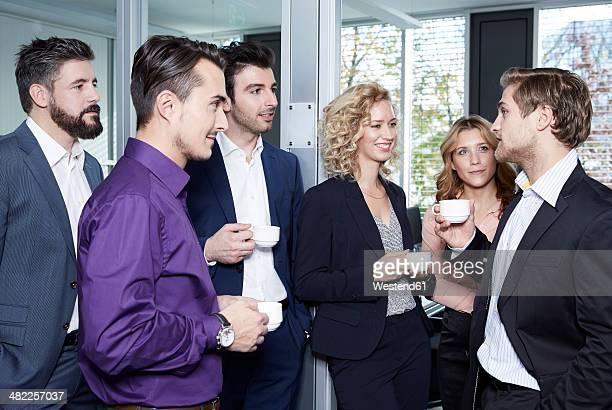 Germany, Neuss, Business people drinking coffee in office