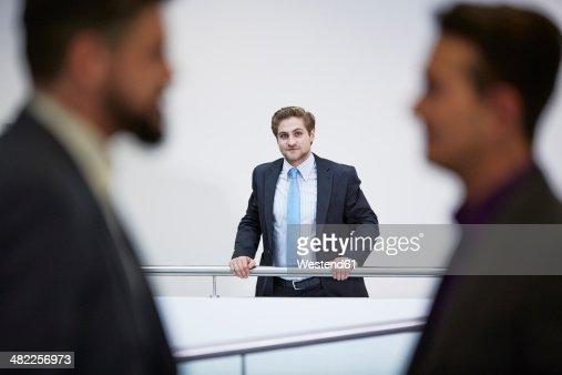 Germany, Neuss, Businessmen talking in corridor