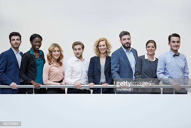Germany, Neuss, Group of business people standing behind railing