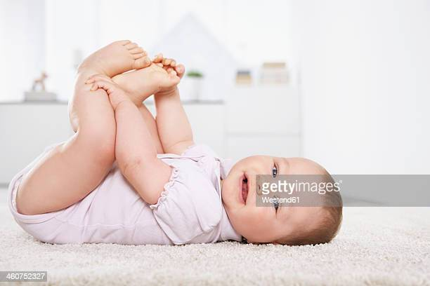Germany, North Rhine Westphalia, Cologne, Baby girl lying on carpet, smiling