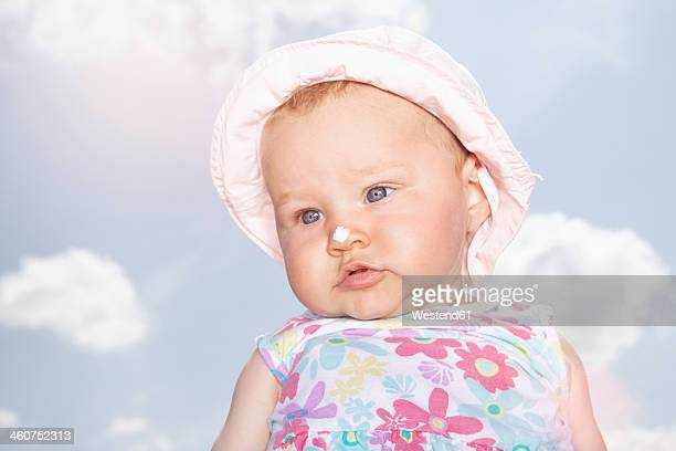 Germany, North Rhine Westphalia, Cologne, Baby girl with suncream on nose, close up