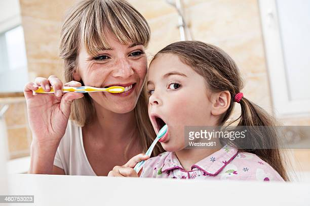 Germany, North Rhine Westphalia, Cologne, Mother and daughter brushing teeth in bathroom