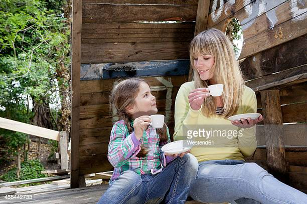 Germany, North Rhine Westphalia, Cologne, Mother and daughter drinking tea, smiling
