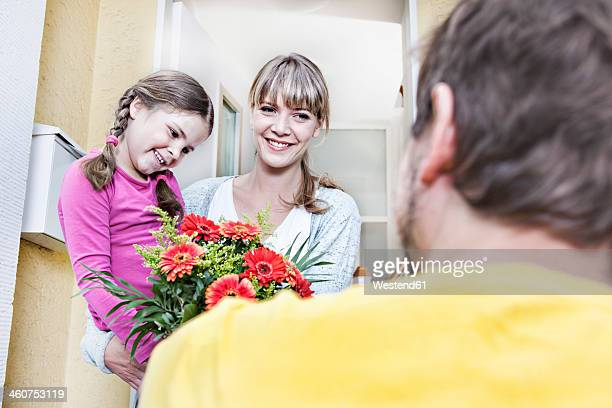 Germany, North Rhine Westphalia, Cologne, Mother and daughter taking flowers from postman, smiling