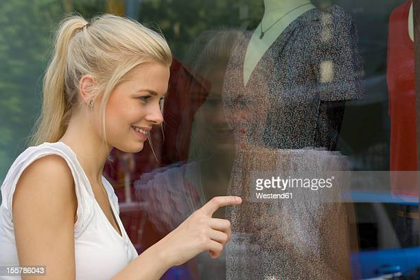 Germany, North Rhine Westphalia, Cologne, Young woman at window shopping