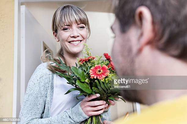 Germany, North Rhine Westphalia, Cologne, Young woman taking flowers from postman, smiling