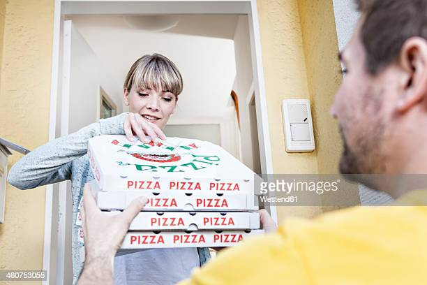 Germany, North Rhine Westphalia, Cologne, Young woman taking pizza boxes from delivery man, smiling
