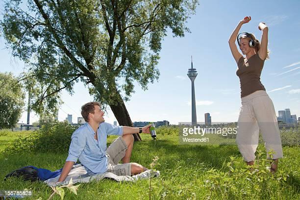 Germany, North Rhine Westphalia, Duesseldorf, Man looking at dancing woman, smiling