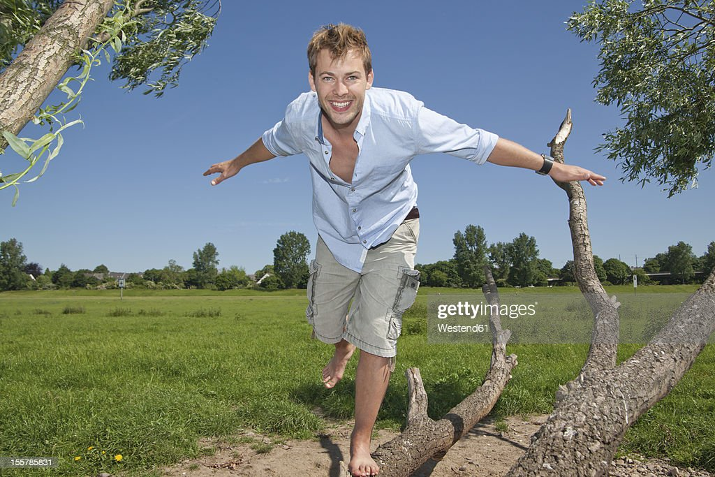 Germany, North Rhine Westphalia, Duesseldorf, Mid adult man playing with tree, smiling, portrait : Photo