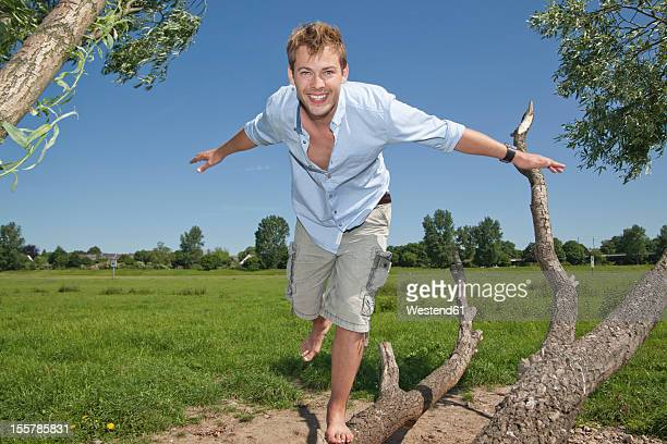 Germany, North Rhine Westphalia, Duesseldorf, Mid adult man playing with tree, smiling, portrait