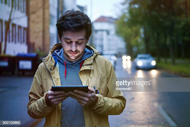Germany, North Rhine-Westphalia, Cologne, young man standing on a street using digital tablet