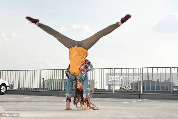 Germany, North Rhine-Westphalia, Cologne, young woman doing handstand on a parking level