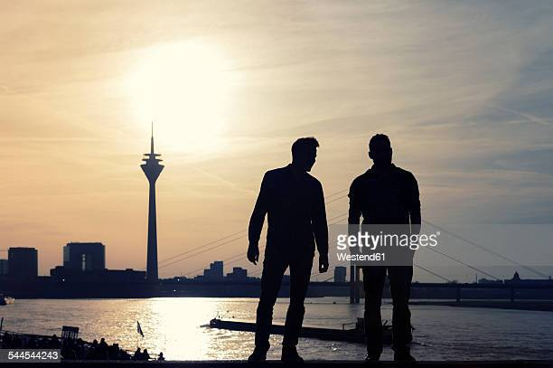 Germany, North Rhine-Westphalia, Duesseldorf, two man looking to Rhine tower and Rhine river at sunset
