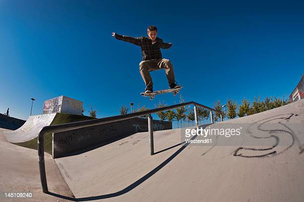 Germany, North Rhine-Westphalia, Duisburg, Skateboarder performing trick on ramp at skateboard park