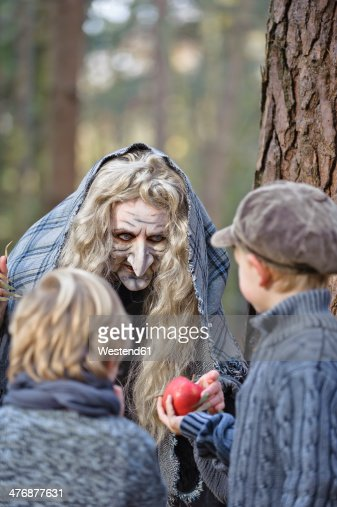 Germany, North Rhine-Westphalia, Moenchengladbach, Scene from fairy tale Hansel and Gretel, witch offering an apple to the children