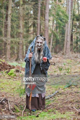 Germany, North Rhine-Westphalia, Moenchengladbach, Scene from fairy tale, witch holding an apple in the woods