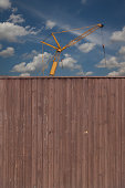 Germany, North Rhine-Westphalia, Neuss, wooden fende and construction crane