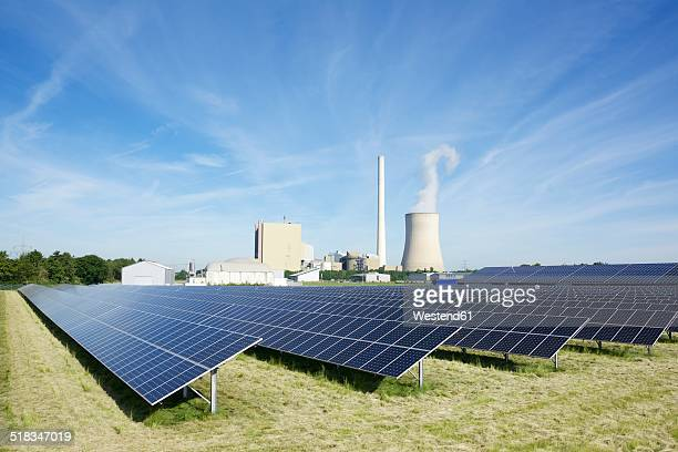 Germany, North Rhine-Westphalia, Petershagen-Lahde, Field with solar panels and a coal-fired power station in the background
