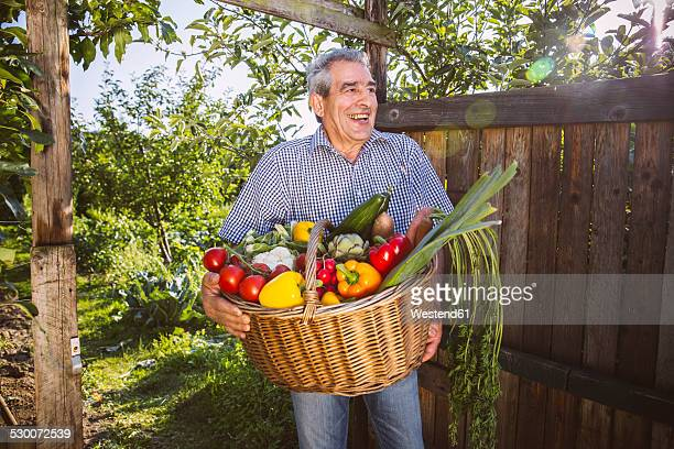 Germany, Northrhine Westphalia, Bornheim, Senior man holding vegetable basket