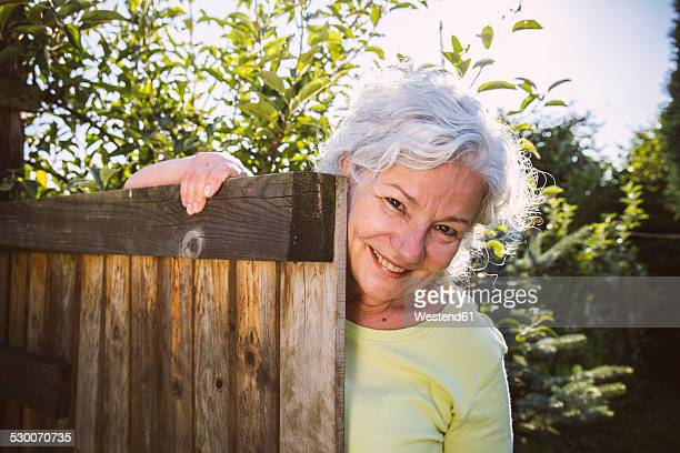 Germany, Northrhine Westphalia, Bornheim, Senior woman leaning on garden gate
