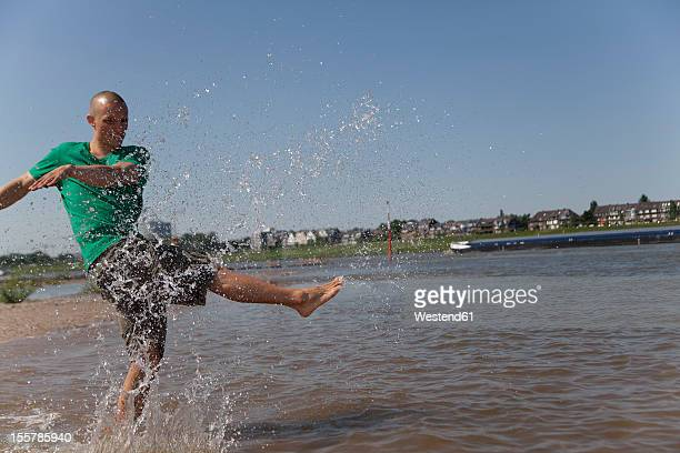 Germany,  North-Rhine-Westphalia, Duesseldorf, Young man splashing in water