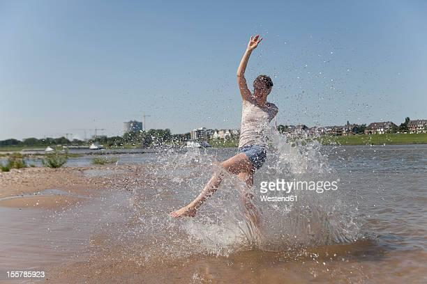 Germany, North-Rhine-westphalia, Duesseldorf, Young woman splashing in water