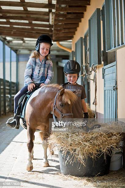 Germany, NRW, Korchenbroich, Boy and Girl at riding stable with mini shetland pony