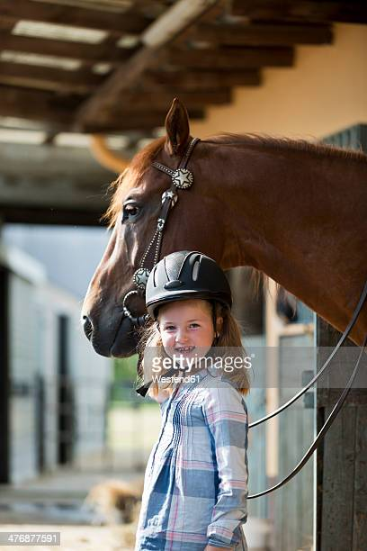 Germany, NRW, Korchenbroich, Little girl with horse in stable