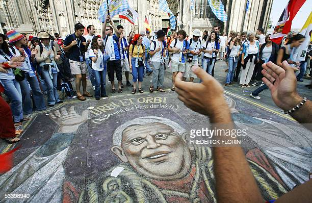 Pilgrims gather around a painted portrait of Pope Benedict XVI on the ground in front of Cologne's cathedral on the second day of the 20th edition of...