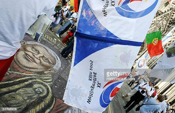 Pilgrims wave flags over a painted portrait of Pope Benedict XVI in front of Cologne's cathedral on the second day of the 20th edition of the World...