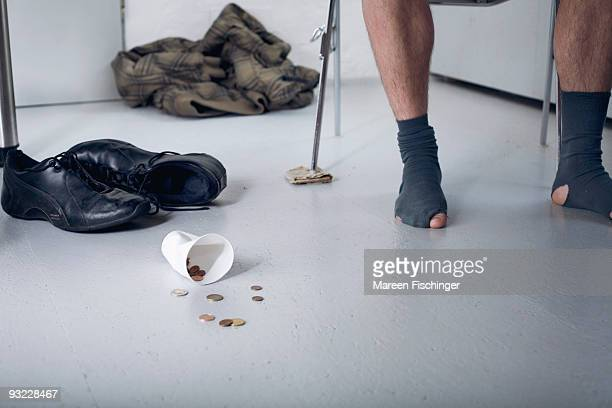 Germany, Plastic cup and coins on floor, shoeless person in background, low section