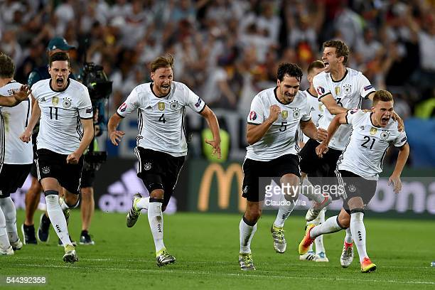 Germany players dash to celebrate their win through the penalty shootout after Jonas Hector scores to win the game after the UEFA EURO 2016 quarter...