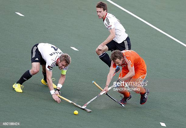 Germany players Maximilian Muller and Oliver Korn vie with Netherlands player Constantijn Jonker during a match in the men's tournament of the Field...