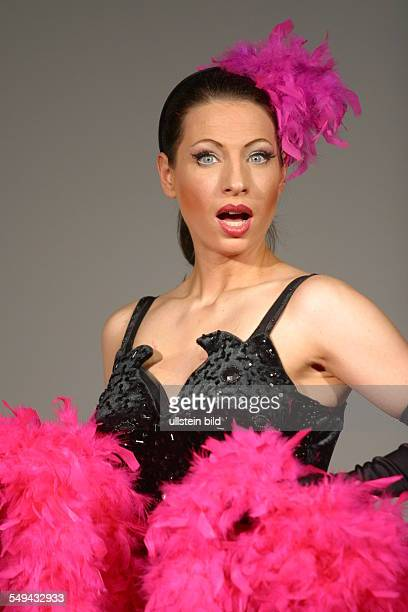 Portrait of a woman dressed in a black dress with a pink feathered boa and pink feathered hair accessories
