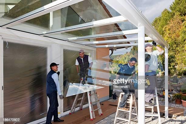 Germany, Rhineland Palatinate, Men assembling glass canopy