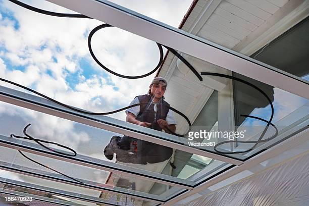 Germany, Rhineland Palatinate, Young man assembling glass canopy