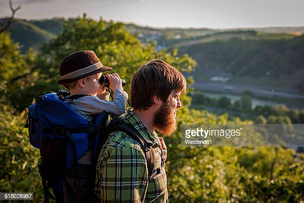 Germany, Rhineland-Palatinate, Moselsteig, father and his little son looking at view with binocular