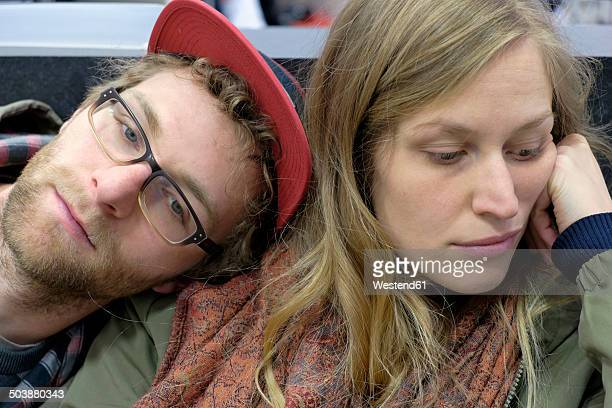 Germany, Rhineland-Palatinate, Trier, Young couple waiting bored in a department store