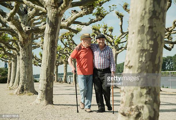 Germany, Rhineland-Palatinate, Worms, two old men walking arm in arm at promenade of Rhine River