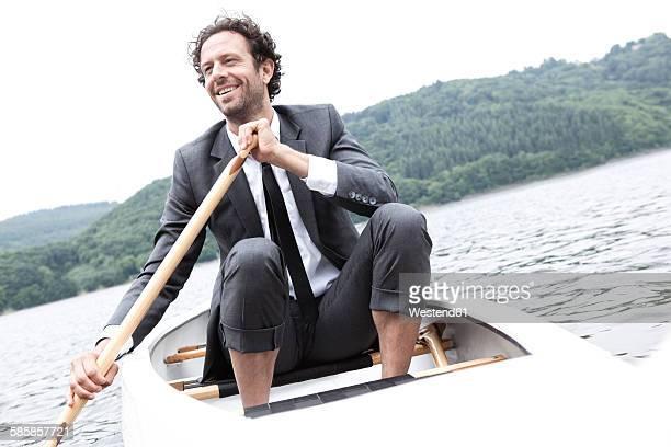 Germany, Rur Reservoir, smiling businessman in canoe