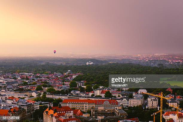 Germany, Saxony, Leipzig, hot air balloon hovering over the city at evening twilight