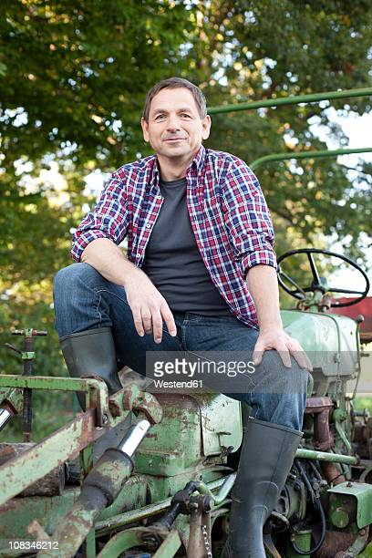 Germany, Saxony, Senior man sitting on tractor, smiling, portrait