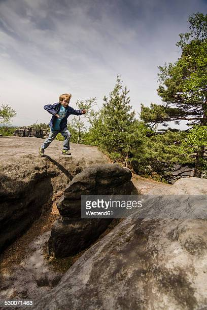 Germany, Saxony, Saxon Switzerland, Lilienstein, Young boy jumping over stones