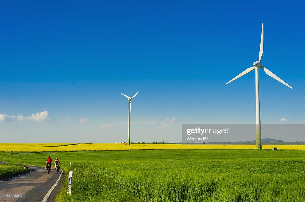 Germany, Saxony, Wind turbines in oilseed rape field