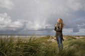 Germany, Schleswig Holstein, Amrum, Woman on grassy sand dune